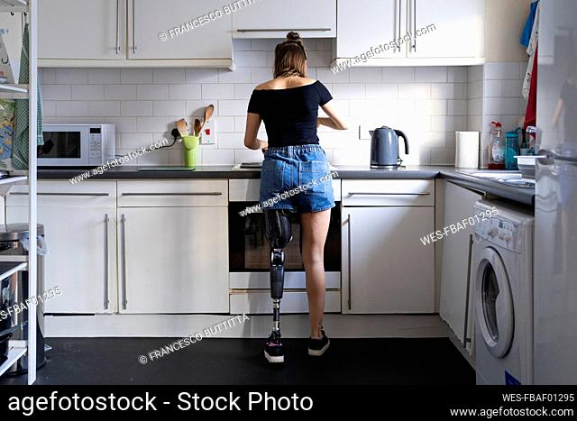 Rear view of young woman with leg prosthesis in kitchen at home