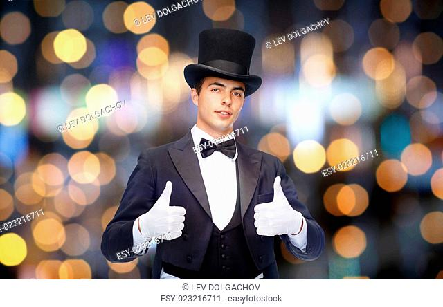 magic, performance, gesture people and show concept - magician in top hat showing thumbs up over nigh lights background