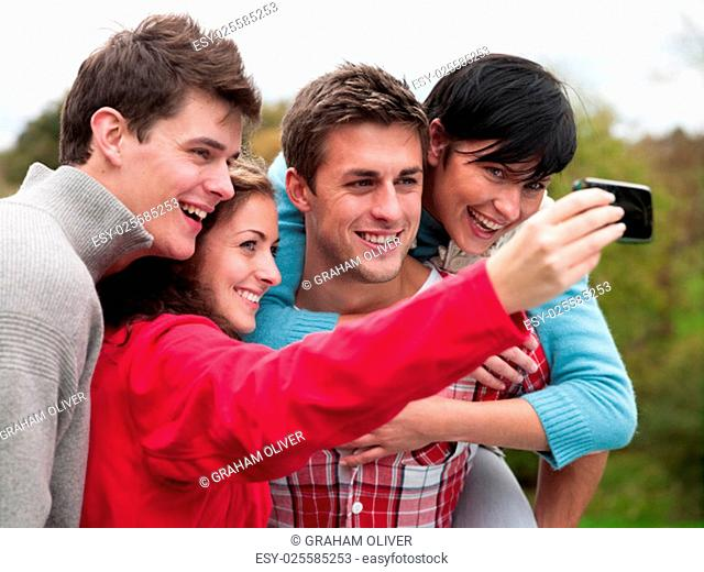 Two couples stand together to take a selfie on a mobile phone outdoors. One girl is being piggybacked by her partner. The other is holding the phone with her...