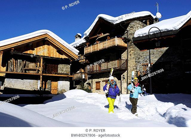 two women with skiing equipment walking through mountain village, France, Savoie, Sainte Foy Tarentaise