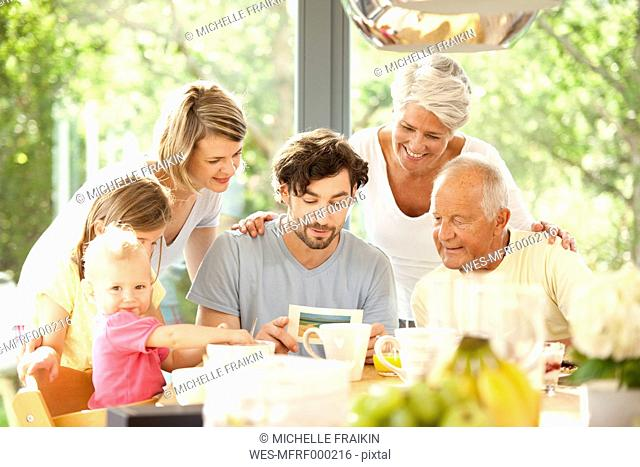 Father with his family reading postcard at breakfast table