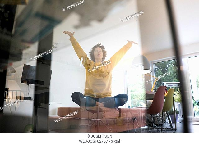 Woman sitting on couch at home in yoga pose