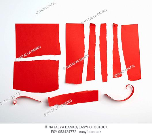 various torn strips of red paper on a white background, flat lay