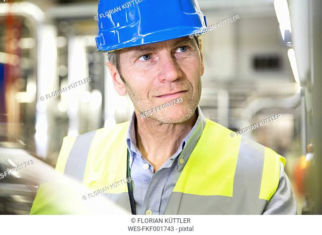 Man wearing reflective vest looking around in industrial plant