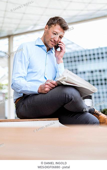 Businessman outside in the city on cell phone