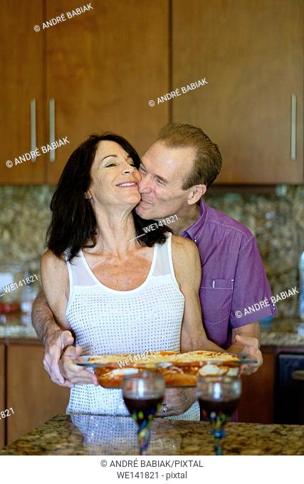 Senior man and woman huggin and kissing in the kitchen while preparing dinner