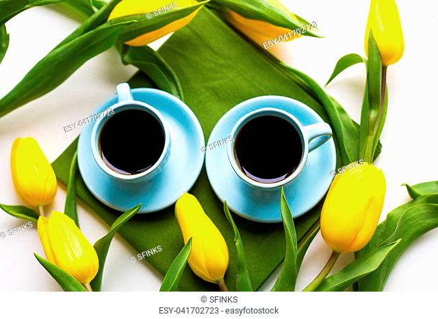 two blue cups of coffee on a table with green cloth and yellow tulips