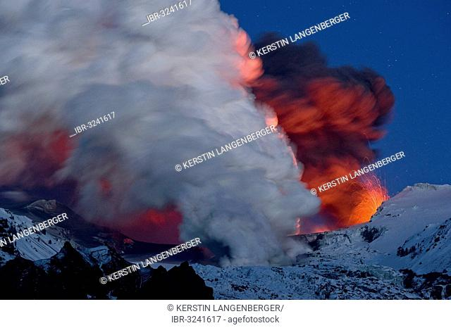 Cloud of ash from Eyjafjallajoekull volcano and a vapour cloud from lava flow in the Gigjoekull glacier tongue, illuminated by an eruption in the crater