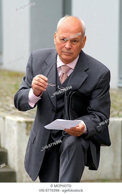 Ein aelterer Mann in Anzug und Krawatte liest eine Notiz 2006 - Germany, 29/05/2006