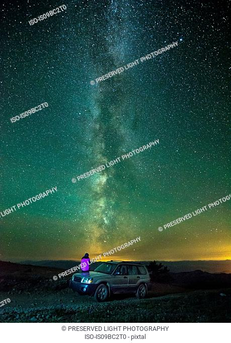 Person sitting on car, looking at view of milky way, rear view, Nickel Plate Provincial Park, Penticton, British Columbia, Canada
