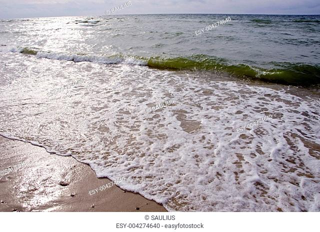 Sea waves water beating shore sand sun reflection