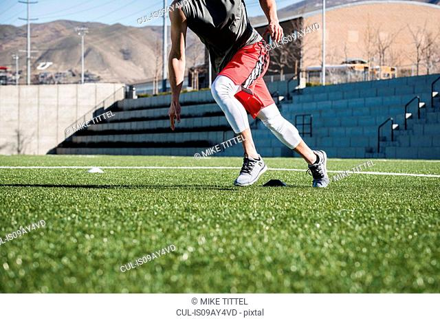 Neck down view of young man running doing agility training with markers on playing field