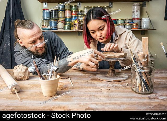 Potter teaching trainee in workshop
