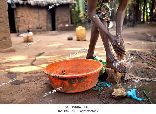 young woman in traditional African clothes washing herself in front of her mud house in the morning, Burundi, Karuzi, Buhiga