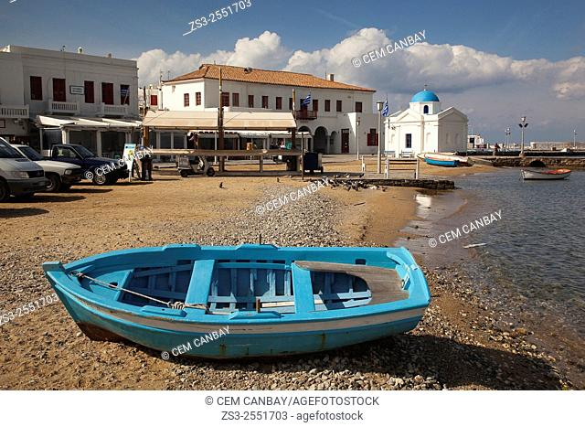 Blue fishing boat at the beach with a blue domed church at the background in town center, Mykonos, Cyclades Islands, Greek Islands, Greece, Europe