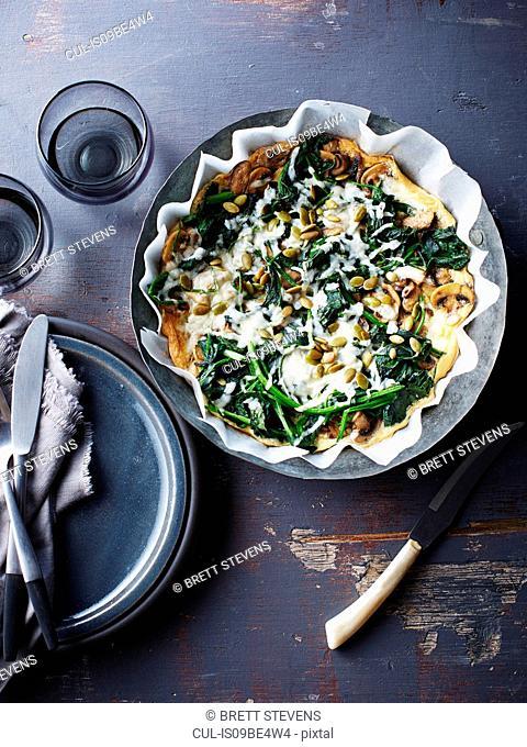 Still life with bowl of spinach feta mushroom frittata, overhead view