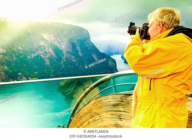 Tourism and travel. Male tourist nature photographer taking photo with camera, enjoying Aurland fjord landscape from Stegastein lookout, Norway Scandinavia