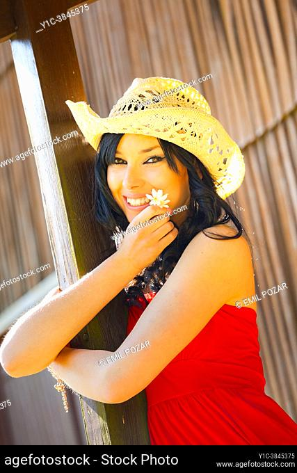 Teen-girl with a stetson straw hat is holding a White flower in hand