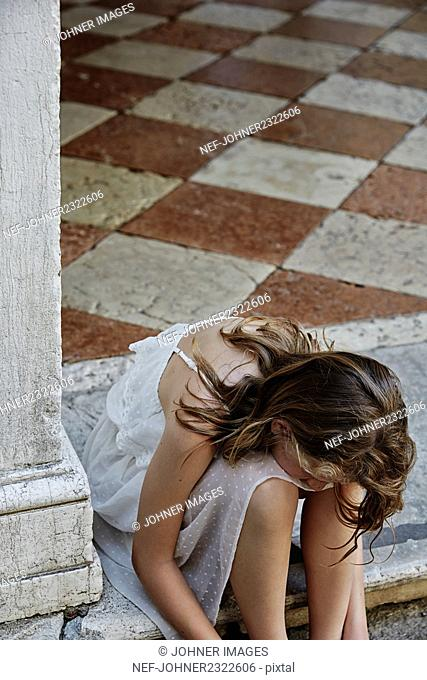 Young woman sitting on stone step