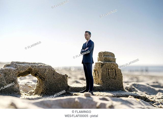 Businessman figurine standing on sand by sand buildings