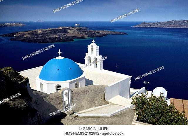 Greece, Cyclades, Santorini island (Thera, Thira), Greek orthodox church with blue dome in the village of Fira overlooking the caldera and the volcanic island...