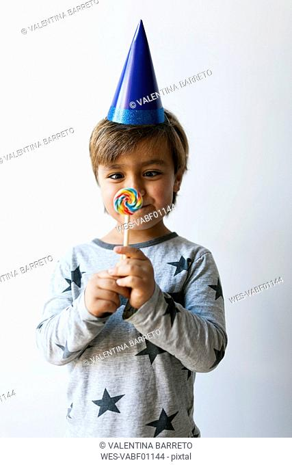 Portrait of cross-eyed little boy with lollipop and blue party hat