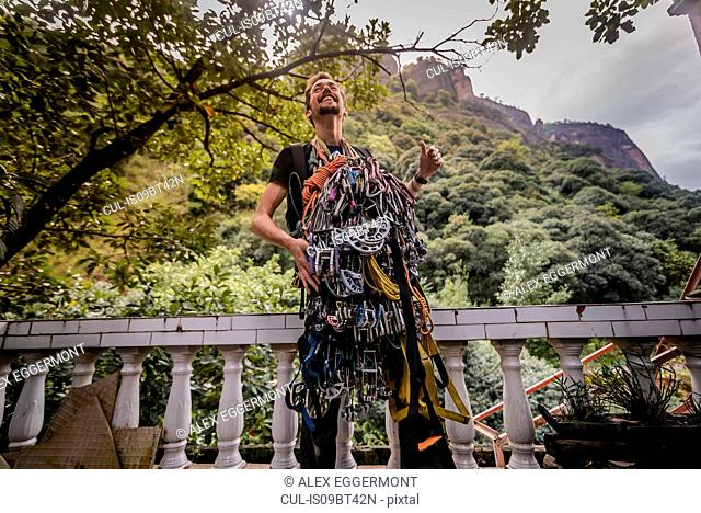 Rock climber covered with safety harness, Liming, Yunnan, China