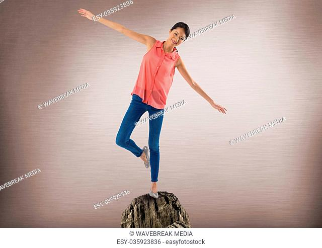 Woman balancing on rock with mystic background