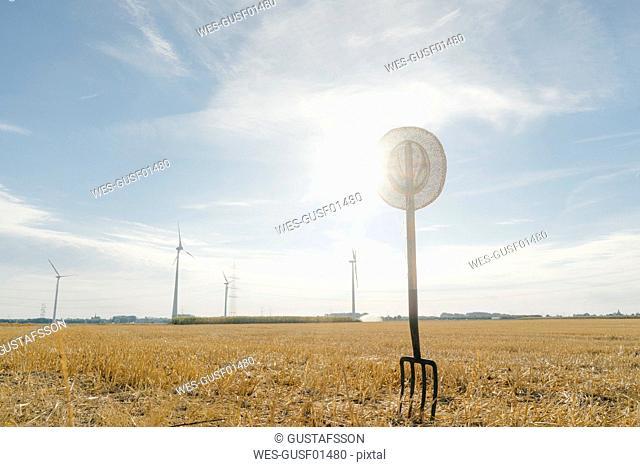 Pitchfork in field in rural landscape with wind turbines in background