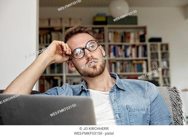 Portrait of pensive man with laptop in the living room