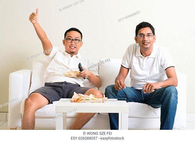 Friendship, sports and entertainment concept. Happy male friends watching sports together on tv at home