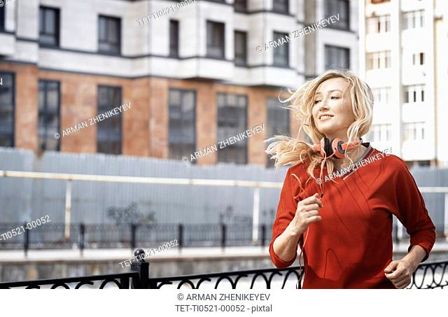 Woman with headphones jogging in city