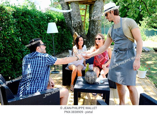 Group of young and cheerful people having a toast in a garden party outdoor in the backyard during summer holiday