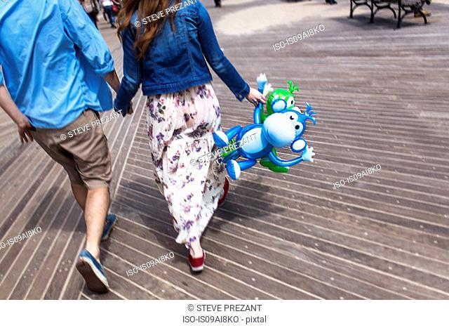 Cropped rear view of couple holding hands on boardwalk