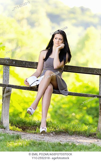 Teen girl in park crossed legs