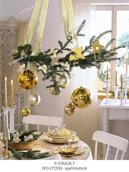 Spruce branch with tree ornaments hanging over table