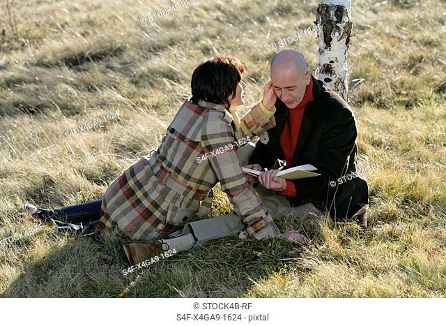 Mature couple sitting on grass, he reading to her