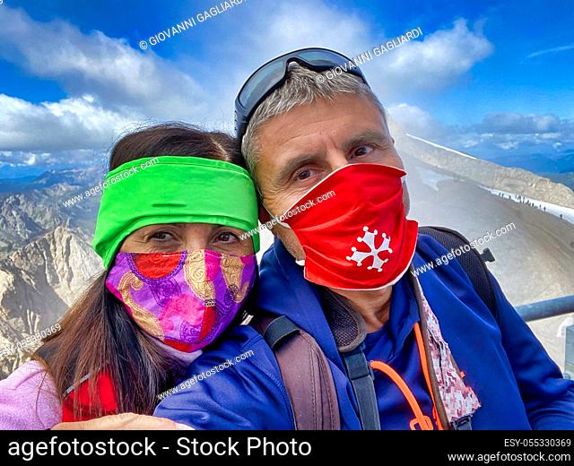 Happy couple wearing health masks during a mountain excursion