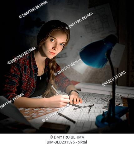 Caucasian woman drawing on blueprint at night