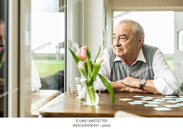 Portrait of senior man looking through window