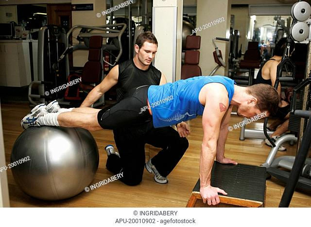 Men training in gym with instructor showing student moves