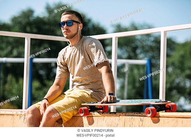 Young man with earbuds and longboard sitting in skatepark