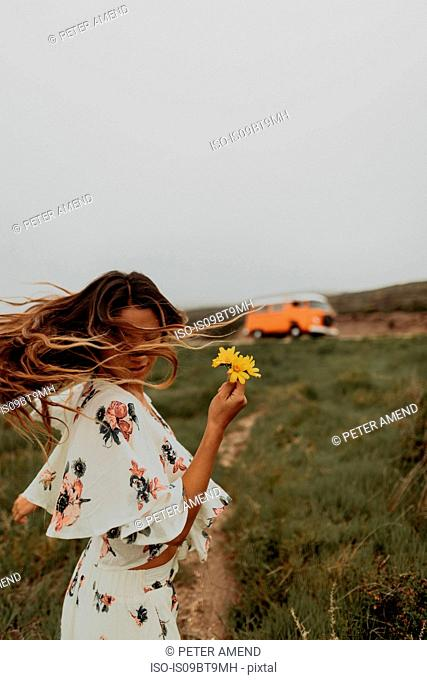 Young woman with wildflowers dancing at coast, Jalama, California, USA