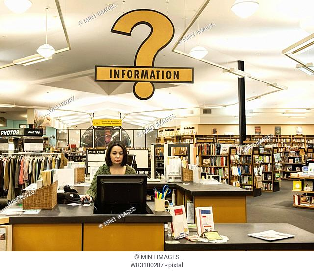 Caucasian female employee working at a computer at the front desk of a book store