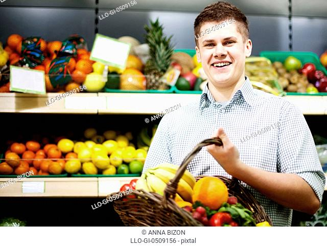 Young man standing the front of shopping shelves Debica, Poland