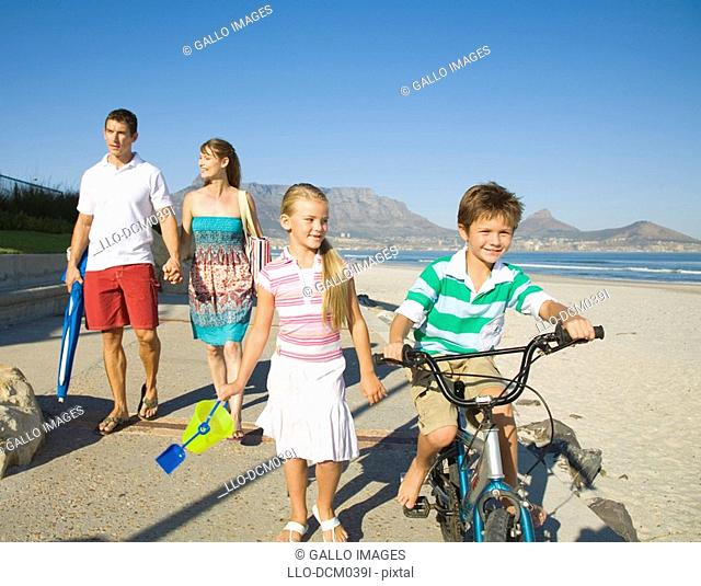 Family going for a stroll on the beach with Table Mountain in the background, Cape Town, Western Cape Province, South Africa