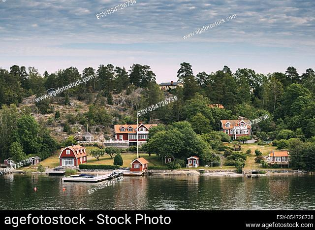 Sweden. Many Beautiful Red Swedish Wooden Log Cabins Houses On Rocky Island Coast In Summer Sunny Evening. Lake Or River Landscape