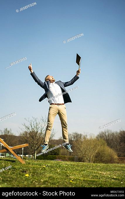Excited businessman holding laptop while jumping on grass at park against clear sky during sunny summer day