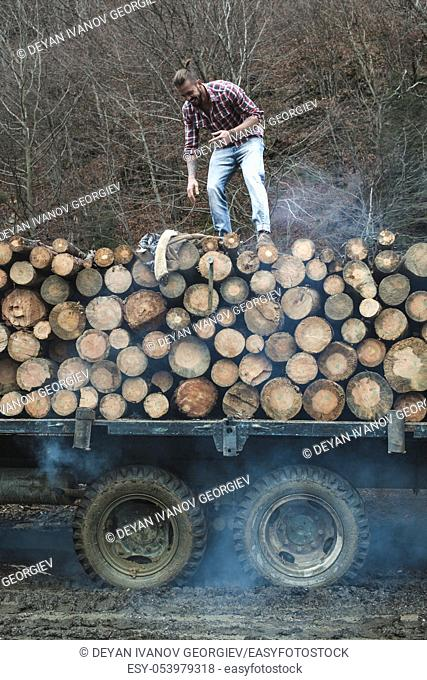 Young man on vintage truck with logs in the forest