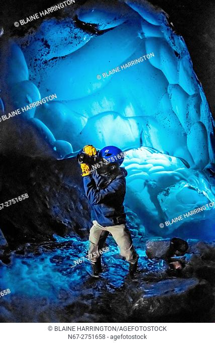 Photographer taking pictures inside an ice cave at Mendenhall Glacier, Juneau, Alaska USA